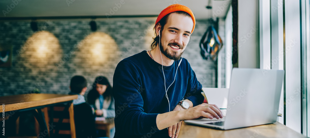 Fototapeta Portrait of happy smiling hipster guy enjoying time for favourite music playlist during e learning in cafeteria, positive male teenager in headphones rest indoors sitting at table with laptop device