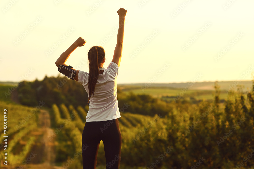 Fototapeta Girl raised her hands up at a training on the nature on the morning.