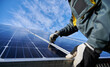 canvas print picture - Close up of man technician in work gloves installing stand-alone photovoltaic solar panel system under beautiful blue sky with clouds. Concept of alternative energy and power sustainable resources.