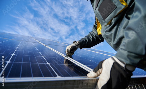 Obraz Close up of man technician in work gloves installing stand-alone photovoltaic solar panel system under beautiful blue sky with clouds. Concept of alternative energy and power sustainable resources. - fototapety do salonu