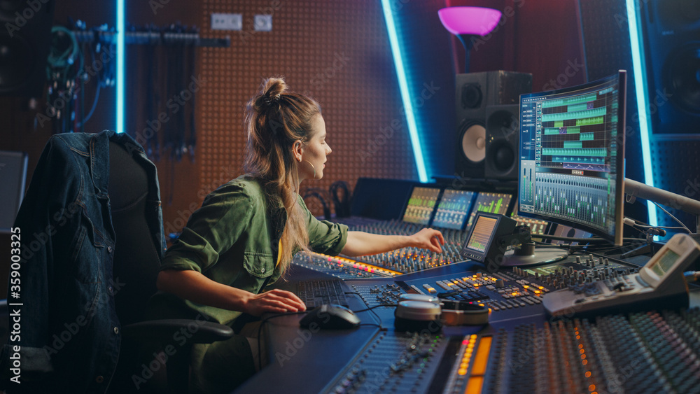 Fototapeta Beautiful Female Audio Engineer Working in Music Recording Studio, Uses Mixing Board and Software to Create Modern Sound. Creative Girl Artist Musician Working on Control Desk to Produce New Song