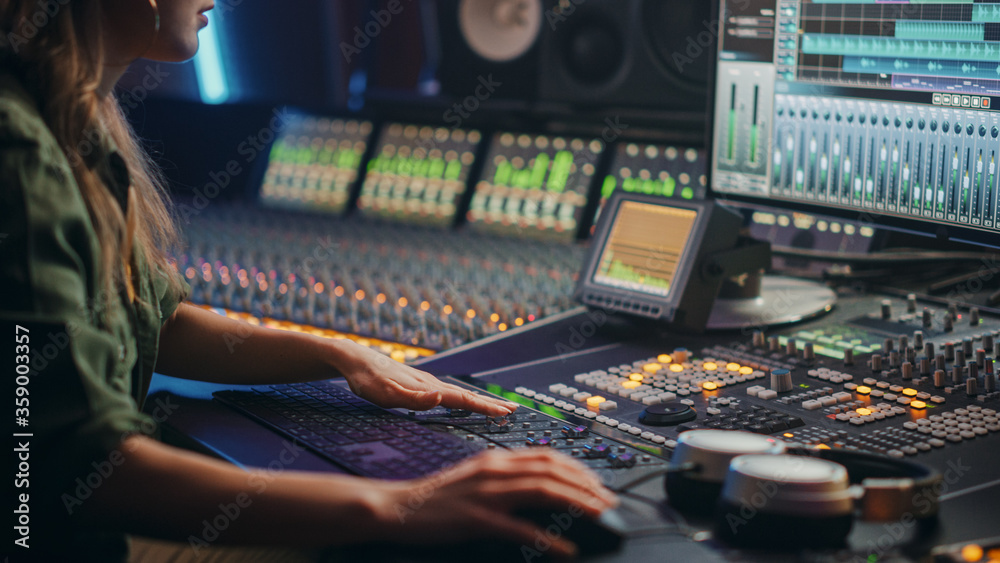Fototapeta Beautiful, Stylish Female Audio Engineer, Producer Working in Music Recording Studio, Uses Mixing Board, Software to Create Cool Song. Creative Girl Artist Musician Working.