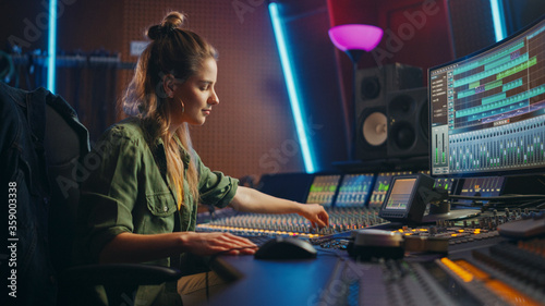 Fototapeta Beautiful, Stylish Female Audio Engineer and Producer Working in Music Recording Studio, Uses Mixing Board and Software to Create Cool Song. Creative Girl Artist Musician Working to Produce New Song obraz