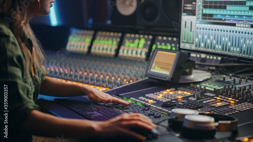 Fototapeta Beautiful, Stylish Female Audio Engineer, Producer Working in Music Recording Studio, Uses Mixing Board, Software to Create Cool Song. Creative Girl Artist Musician Working. obraz