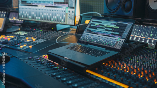 Photo Modern Music Record Studio Control Desk with Laptop Screen Showing User Interface of Digital Audio Workstation Software