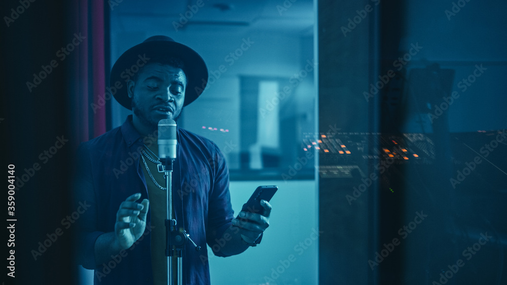 Fototapeta Portrait of Successful Young Black Artist, Singer, Performer Singing His Hit Song for the New Album. Wearing Stylish Hat, Holding Smartphone and Standing in Music Record Studio Soundproof Room.