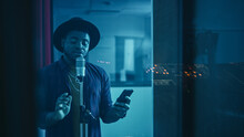Portrait Of Successful Young Black Artist, Singer, Performer Singing His Hit Song For The New Album. Wearing Stylish Hat, Holding Smartphone And Standing In Music Record Studio Soundproof Room.