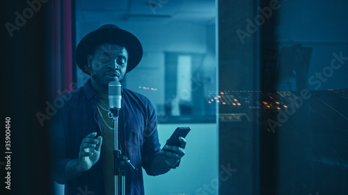 Fotografia Portrait of Successful Young Black Artist, Singer, Performer Singing His Hit Song for the New Album