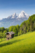 Leinwandbild Motiv Summer mountain scenery in the Alps with blooming meadows and traditional mountain cabin