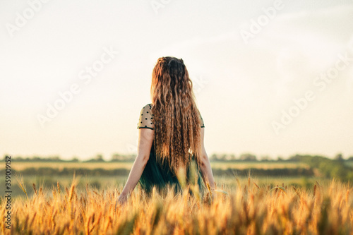 Obraz Beautiful woman in green dress walkink across field and touches ears of wheat with hand at sunset light, girl enjoying summer nature landscape - fototapety do salonu