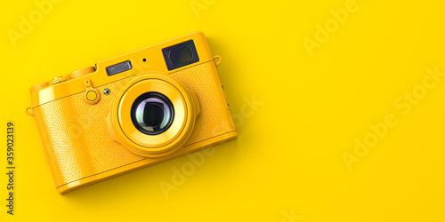 Fotografia Yellow vintage photo camera on yellow background.