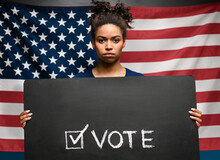 African American Woman Holding Banner With VOTE Sign