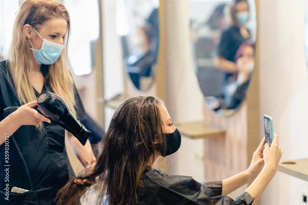 Fototapeta Hairdresser drying her client's hair with a hairdryer wearing protective masks in a beauty centre.