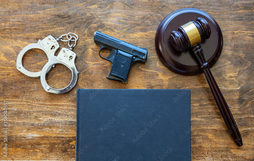 Fototapeta Law, crime, punishment concept. Judge gavel, handgun, handcuffs and a black blank legal book on wooden brown desk background, space.