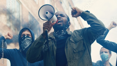 Fotografiet African American young handsome guy with scarf on face protesting in middle of crowd of protesters and screaming mottos in megaphone