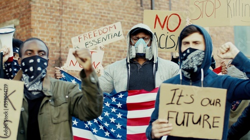 Fotografiet African American and Caucasian men in respirators and masks with American flag shouting mottos and taking part in demonstration for black people human rights and equality