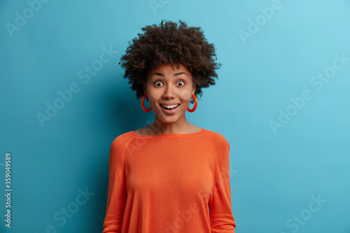 Portrait of happy surprised Afro American woman stands with amazed face expressi Canvas Print