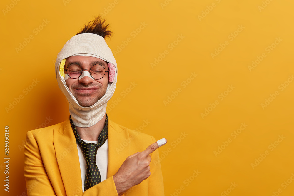 Fototapeta Cheerful man with funny face expression, closes eyes, recovers after injury, has abrasions and bruises, has head concussion, plaster on nose and finger, shows way to chemist, isolated on yellow wall