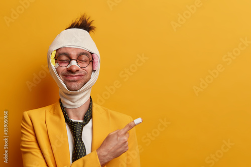 Cheerful man with funny face expression, closes eyes, recovers after injury, has Fotobehang