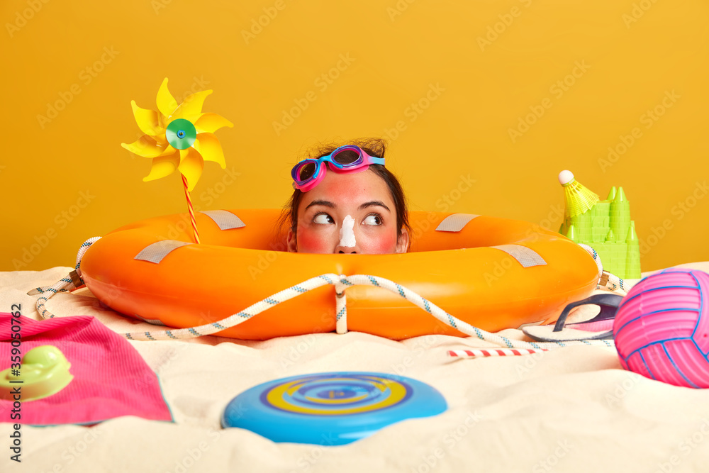 Fototapeta Summer vacation and holiday resort concept. Pensive young woman with goggles on forehead, looks aside thoughtfully, enjoys sun, applies sunscreen on face, poses at sandy beach with different items