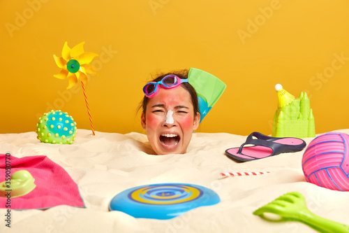 Emotional young Asian woman spends leisure time at beach, buried in sand, swimmi Fototapete