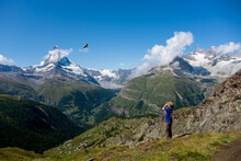 Young Boy Observing A Bird Of Prey Through Binoculars With Swiss Mountains As A Backdrop.