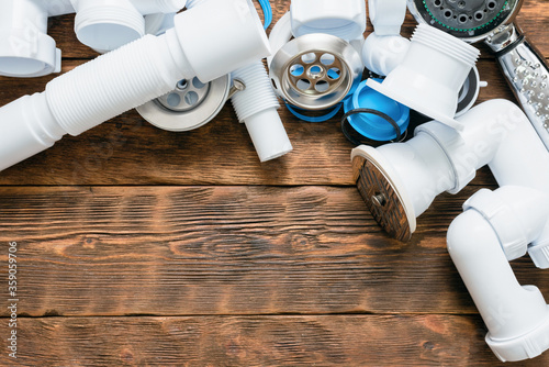 Shower plastic siphon parts on white wooden floor background. Wallpaper Mural