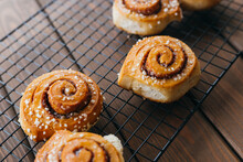 Cinnabons Won A Wire Rack On The Table. Food Concept. Homemade Sweet Pastries On A Wooden Background. Top View