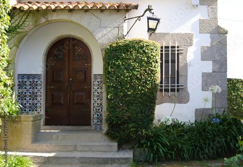 Parte da frente de uma casa com um alpendre em forma de arco, candeeiro antigo e Wallpaper Mural