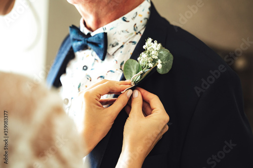 Close up female hands attaching wedding boutonniere on man's suit Canvas Print