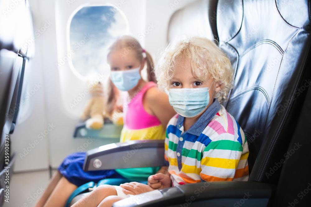 Fototapeta Child in airplane in face mask. Virus outbreak.