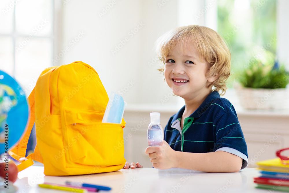 Fototapeta Backpack of school child. Face mask and sanitizer.