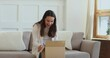 Happy positive young mixed race woman sitting on sofa, unboxing delivery carton parcel, satisfied with purchase in internet store. Smiling female client feeling excited of fast shipping service.