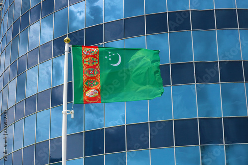 Flag of Turkmenistan against the glass windows of a multi-storey office building or business center Wallpaper Mural