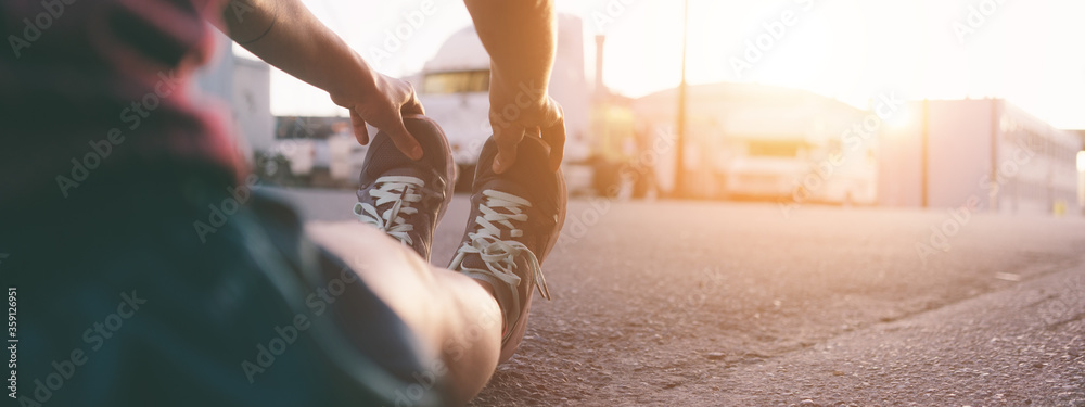 Fototapeta Fit woman runner warming up before workout, sunset time. Wide screen, panoramic