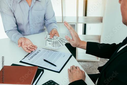 Fényképezés Businessperson refusing bribe given money by partner with anti bribery corruption concept