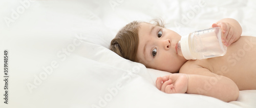 Cute little baby with bottle on bed, space for text Fototapet