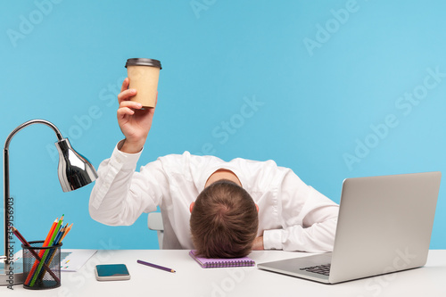 Fotografía Exhausted male employee feeling fatigue lying on table and raising coffee cup, lack of energy in morning office, tired of stress problems sleeping at workplace, overwork concept