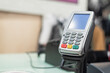 Payment pos terminal on a store counter background.