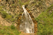 Waterfall Flowing Down Between A Caucasus Mountains Of North Caucasus