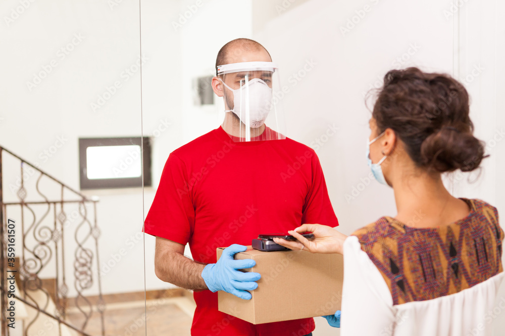 Fototapeta Delivery man wearing protection mask while woman paying package.