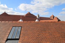 An Expanse Of Red Tiled Roofs With A Roof Window.