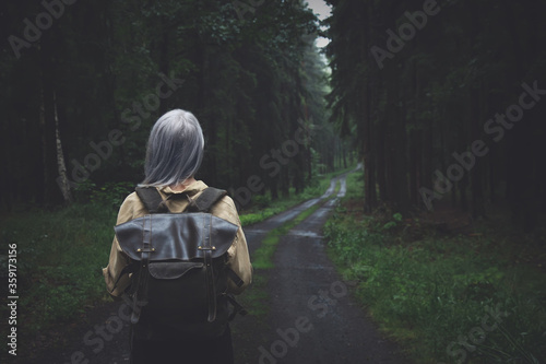 Blonde woman with backpack in rainy day in forest Fotobehang