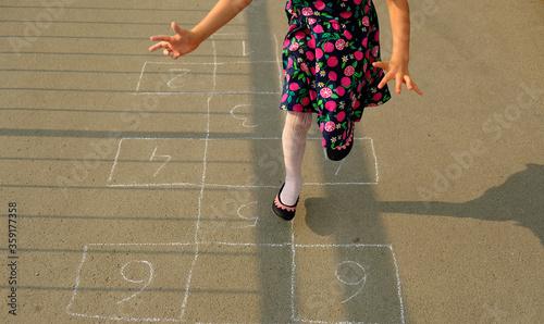 Dziewczynka bawiąca się w skakanie w klasy - fototapety na wymiar