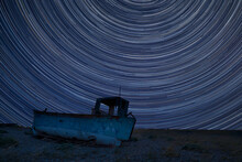 Digital Composite Image Of Star Trails Around Polaris With Abandoned Fishing Boat On Beach Landscape