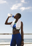 Fit woman drinking water after workout session