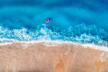 Aerial View Of A Young Woman Swimming With The Donut Swim Ring In Transparent Blue Sea With Waves At Sunset In Summer In Turkey. Tropical Landscape With Girl, Azure Water, Sandy Beach. Top View