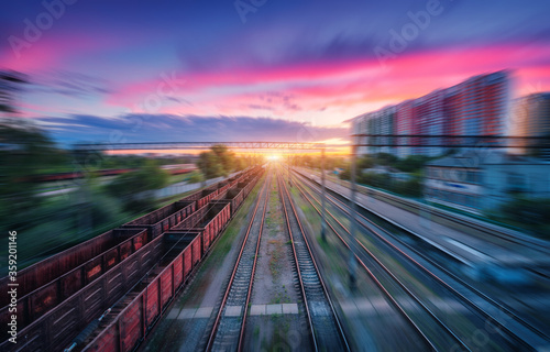 Fotomural Aerial view of railroad and colorful sky with clouds at sunset with motion blur effect in summer