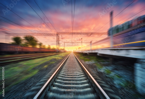 Cuadros en Lienzo Railroad and beautiful sky with clouds at sunset with motion blur effect in summer