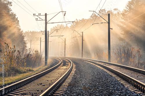 Fotografía Railroad in beautiful forest in fog at sunrise in autumn